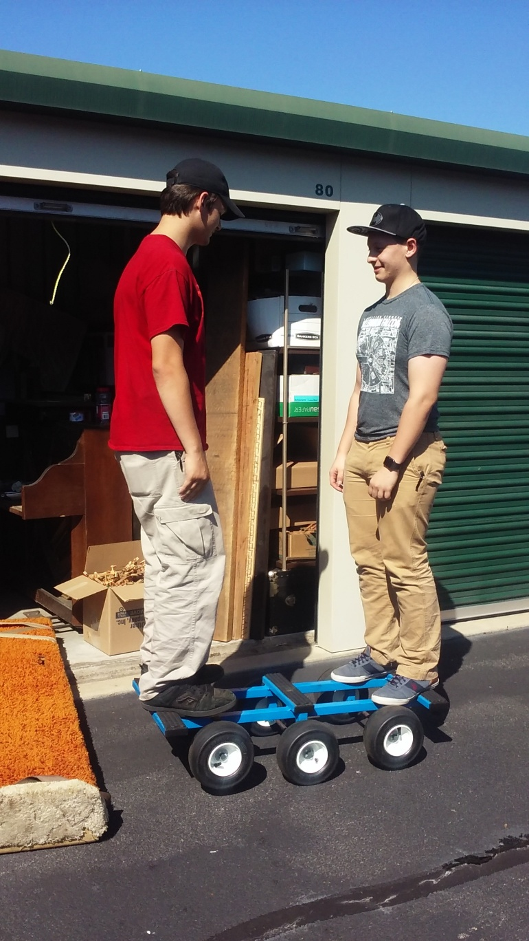 two young men standing on a piano dolly