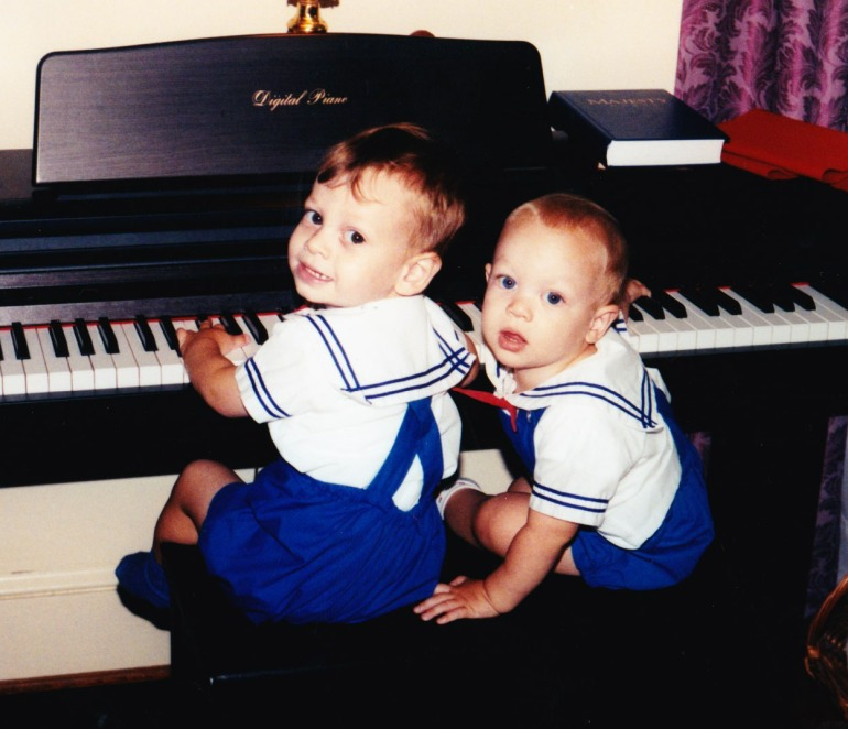 two young boys sitting at the piano